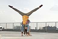 Germany, North Rhine-Westphalia, Cologne, young woman doing handstand on a parking level - FEXF000142