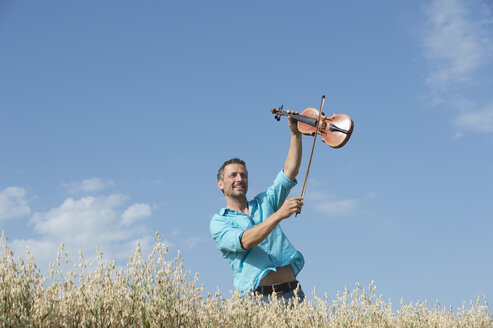 Germany, Bavaria, Starnberg Region, Man playing violin in field - CRF002600