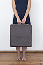 Woman standing holding suitcase - MW000063