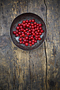 Bowl of red currants, Ribes rubrum, on dark wooden table, elevated view - LVF001608