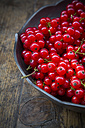 Bowl of red currants, Ribes rubrum, on dark wooden table, partial view - LVF001613