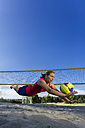 Germany, Young woman playing beach volleyball - STSF000442