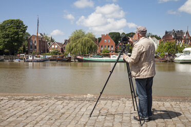 Germany, Lower Saxony, Leer, senior man taking a picture of the museum harbour with his camera - WIF000894
