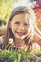 Portrait of smiling little girl lying on a meadow in the garden - SARF000729