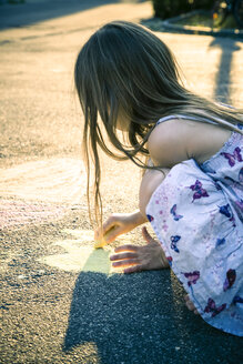 Little girl painting with crayons on tarmac - SARF000734