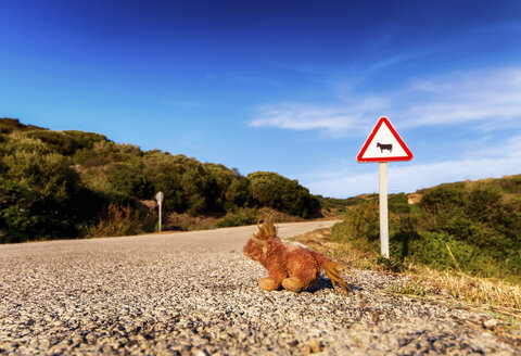Spain, Balearic Islands, Menorca, Road sign at a road with soft toy - SMAF000224