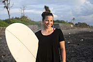 Indonesia, Bali, Canggu, portrait of happy young woman with surfboard on the beach - FAF000055