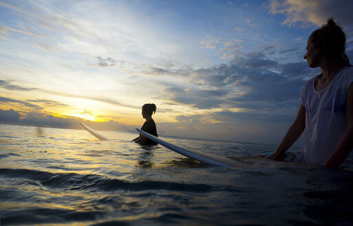 Indonesia, Bali, Canggu, two female surfer in the water watching sun - FAF000057
