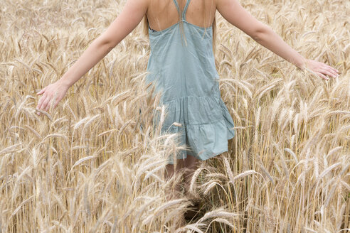 Young woman with outstretched arms walking through a rye field, partial view - DRF000950