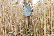 Young woman walking through a rye field, partial view - DRF000953