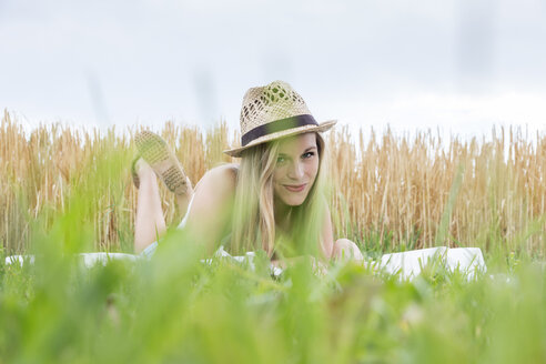 Portrait of smiling young woman with hat lying on a blanket in front of a rye field - DRF000967