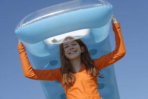 Portrait of smiling girl carrying air mattress on her head wearing sun protection longsleeve - LBF000834