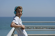Portrait of teenage boy with headphones in front of the sea - LBF000857