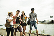 Group of friends walking at the riverside - UUF001390