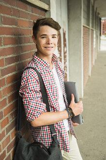 Smiling teenage boy leaning against brick wall - UUF001421