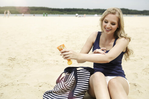 Smiling young woman sitting on the beach using suncream - GDF000356