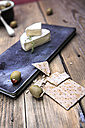 cheese plate and olives on chopping board - VTF000341
