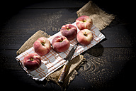 Six doughnut peaches, Prunus persica var. platycarpa, and a knife on cloth and dark wooden table - MAEF008806