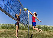Two young women playing beach volleyball - STSF000456