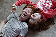 Portrait of brother and sister lying on the floor taking selfies with smartphone - LB000839