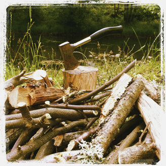 Belgium, Province Luxembourg, The Ardennes, axe on tree stump, pile of fire wood for campfire and barbeque - GWF003015