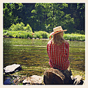 Belgium, Province Luxembourg, The Ardennes, Woman sitting at Semois river - GWF003043