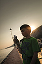 Italy, Veneto, Garda, Lake Garda, boy taking a photo by sunset - SBDF001049
