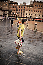 Italy, Tuscany, Siena, Piazza del Campo, boy walking through puddles by rain - SBDF001051