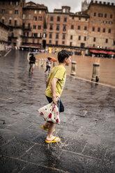 Italy, Tuscany, Siena, Piazza del Campo, boy walking through puddles by rain - SBDF001051