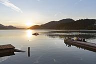 Austria, Salzburg State, Fuschlsee Lake, Fuschl am See, Wooden boardwalk and people at sunset - SIE005687