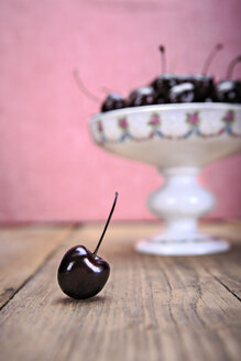 Etagere of cherries on wooden table with one cherry in the foreground - VTF000345