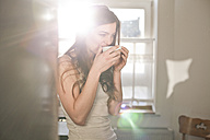 Portrait of young woman drinking tea in the morning - FEXF000148