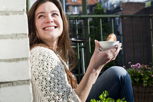 Smiling young woman with cup of tea sitting on her balcony - FEXF000168