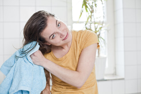 Portrait of young woman drying her hair with towel in the bathroom - FEXF000171