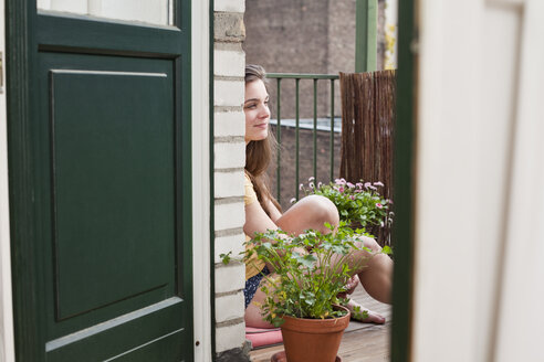 Young woman sitting on her balcony - FEXF000175