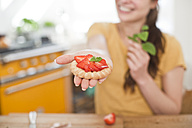 Young woman with strawberry tartelet, partial view - FEXF000181