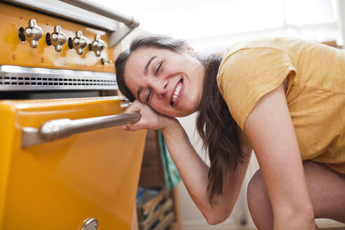 Portrait of smiling young woman in front of her oven - FEXF000183