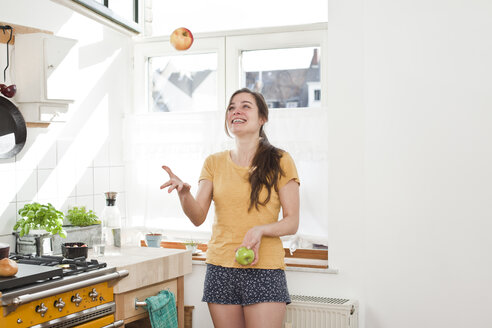 Smiling young woman juggling with two apples in her kitchen - FEXF000186
