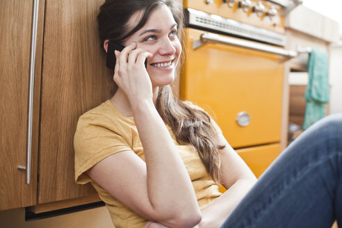 Portrait of smiling young woman telephoning in her kitchen - FEXF000190