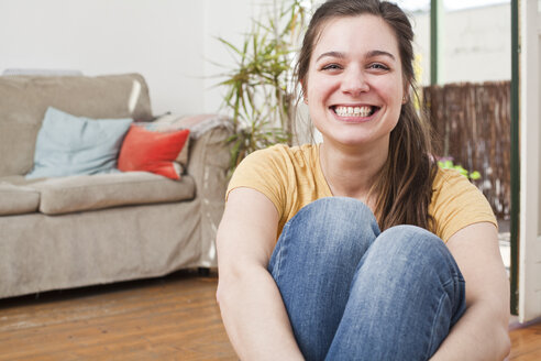 Portrait of grinning young woman sitting in her living room - FEXF000198