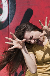 Portrait of young woman making a face in front of a graffiti - FEXF000208