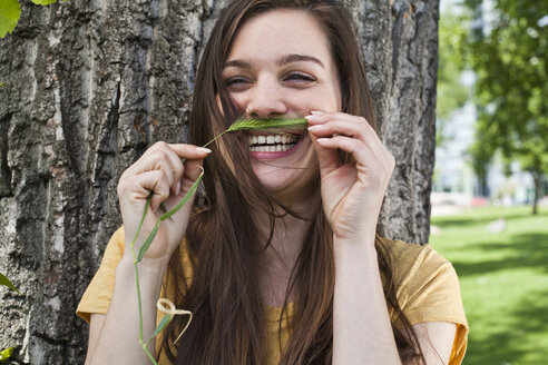 Portrait of young woman holding spike in her face like a moustache - FEXF000219