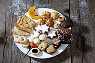 Plate of different Christmas cookies on grey wood - CSF021992