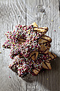 Stack of decorated Christmas cookies on grey wood - CSF021998