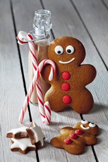 Two gingerbread men, bottle of cocoa, sugar canes and cinnamon stars on grey wood - CSF022001
