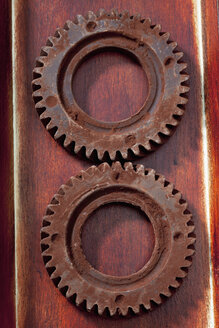 Two cog wheels made of chocolate lying on wood - CSF022019
