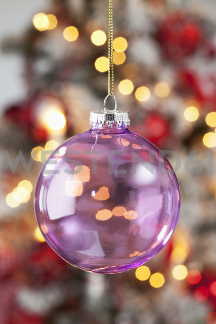 Transparent Christmas bauble hanging in front of blurred flares - CSF022031