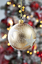 Golden Christmas bauble with white stars hanging in front of blurred flares - CSF022034