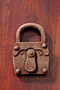 Padlock made of chocolate lying on wood - CSF022035