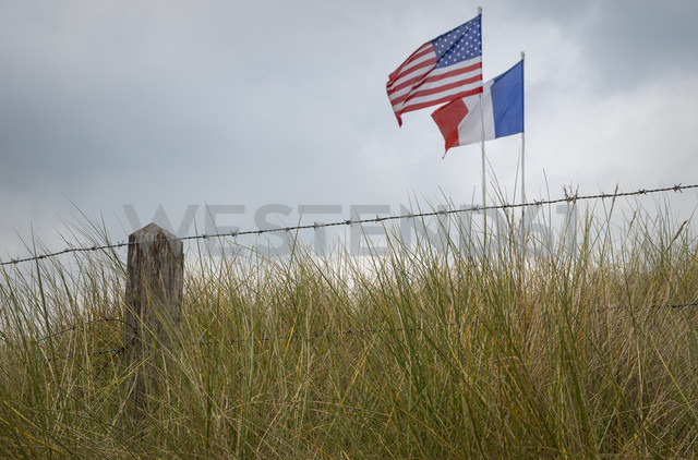France, Lower Normandy, Manche, Sainte Marie du Mont, Utah Beach, Barbed wire fence and French and US flag - MKF000046